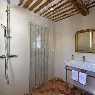 Réalisation d'une salle d'eau méditerranéenne avec une douche d'angle, un mur beige, un sol en carreau de terre cuite, un plan vasque, un sol rouge et aucune cabine.
