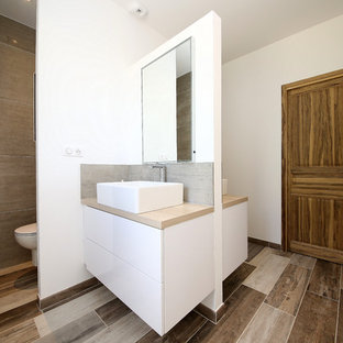 Design ideas for a mediterranean shower room in Marseille with beaded cabinets, a wall mounted toilet, grey tiles, white walls, a console sink, wooden worktops and brown floors.