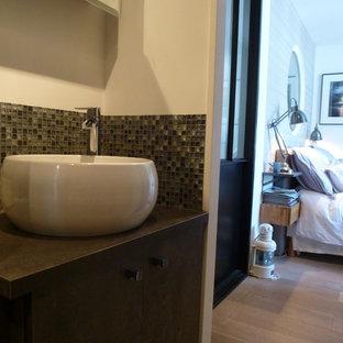 Foto di una stanza da bagno con doccia contemporanea di medie dimensioni con ante di vetro, ante grigie, WC monopezzo, piastrelle grigie, piastrelle in ceramica, pareti grigie, pavimento con piastrelle in ceramica, lavabo da incasso e top in cemento