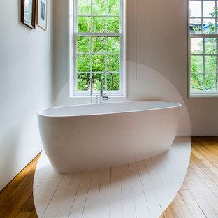 Idées déco pour une grande salle de bain principale contemporaine avec une baignoire indépendante, un mur beige et un sol en bois clair.