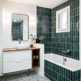 Modernes Badezimmer mit flächenbündigen Schrankfronten, weißen Schränken, Eckbadewanne, grünen Fliesen, Metrofliesen, weißer Wandfarbe, Aufsatzwaschbecken, Waschtisch aus Holz, brauner Waschtischplatte, Einzelwaschbecken und freistehendem Waschtisch in Bordeaux