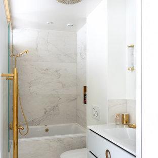 Cette photo montre une petit salle d'eau tendance avec des portes de placard blanches, une baignoire posée, une douche ouverte, un WC suspendu, un carrelage gris, des carreaux de porcelaine, un mur blanc, un lavabo intégré, un sol gris, un plan de toilette blanc, un placard à porte plane, meuble simple vasque et meuble-lavabo sur pied.