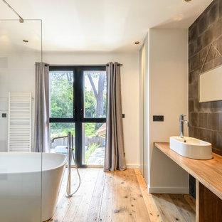 Idée de décoration pour une salle de bain principale design avec un placard sans porte, des portes de placard en bois clair, une baignoire indépendante, une douche ouverte, un mur blanc, une vasque, un plan de toilette en bois et un sol beige.