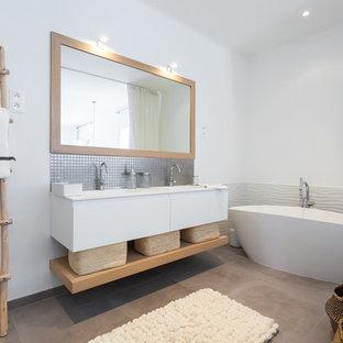 Immagine di una stanza da bagno scandinava con ante lisce, ante bianche, vasca freestanding, pareti bianche, lavabo sottopiano e pavimento beige