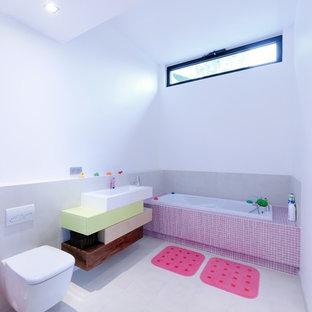 Imagen de cuarto de baño infantil, actual, de tamaño medio, con bañera encastrada sin remate, sanitario de pared, baldosas y/o azulejos grises, paredes blancas, suelo de baldosas de cerámica y lavabo sobreencimera