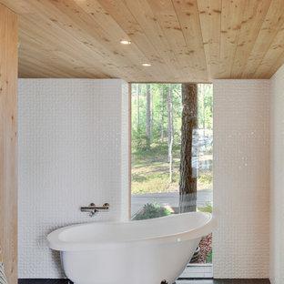 Cette photo montre une salle de bain principale scandinave de taille moyenne avec une baignoire sur pieds, un carrelage blanc, un mur blanc et un sol en ardoise.