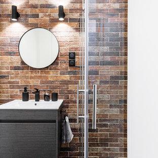 Inredning av ett industriellt litet vit vitt en-suite badrum, med släta luckor, grå skåp, en kantlös dusch, en vägghängd toalettstol, röd kakel, stenkakel, röda väggar, klinkergolv i keramik, ett konsol handfat, bänkskiva i akrylsten, svart golv och dusch med gångjärnsdörr