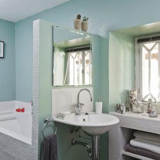 Aménagement d'une salle de bain principale contemporaine de taille moyenne avec un lavabo de ferme, un placard sans porte, une baignoire en alcôve, un carrelage blanc, des portes de placard blanches et un mur bleu.