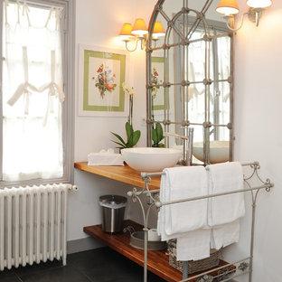 Réalisation d'une salle de bain champêtre de taille moyenne avec une vasque, un plan de toilette en bois, un mur blanc, un placard en trompe-l'oeil et des portes de placard en bois brun.