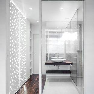 Réalisation d'une petit salle de bain design avec une vasque, un placard sans porte, des portes de placard en bois sombre, un mur blanc et un sol en bois foncé.