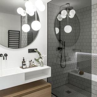 Inspiration pour une salle d'eau design de taille moyenne avec un placard à porte plane, des portes de placard en bois clair, une douche à l'italienne, un carrelage blanc, un carrelage métro, un mur blanc, un sol multicolore et un plan de toilette blanc.
