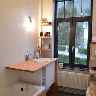 Immagine di una stanza da bagno con vasca sottopiano, piastrelle bianche, pareti bianche, pavimento in linoleum, lavabo a bacinella e top in legno