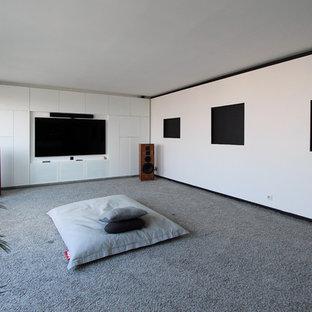 Inspiration pour une grande salle de cinéma design fermée avec un mur blanc, moquette, un téléviseur fixé au mur et un sol gris.