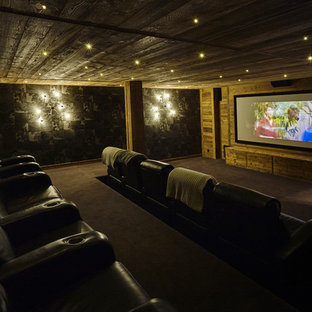 Inspiration for a large rustic enclosed carpeted home theater remodel in Lyon with a projector screen and brown walls