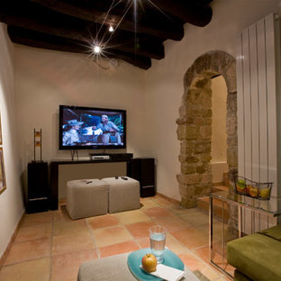 Esempio di un home theatre mediterraneo con pareti bianche, pavimento in terracotta, TV a parete e pavimento rosso