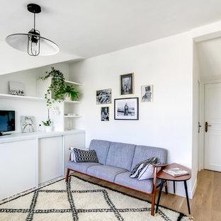 Idée de décoration pour une salle de séjour avec une bibliothèque ou un coin lecture nordique de taille moyenne avec un mur blanc, un sol en bois clair, aucune cheminée et un téléviseur indépendant.