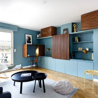 Réalisation d'une salle de séjour design avec un mur bleu, un sol en bois clair et aucune cheminée.