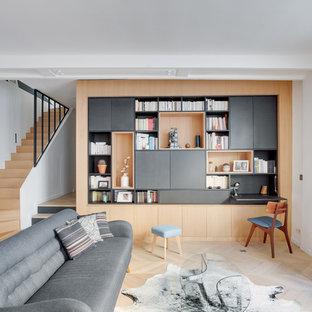 Exemple d'une grande salle de séjour avec une bibliothèque ou un coin lecture tendance ouverte avec un mur blanc, un sol en bois clair, aucune cheminée, un téléviseur dissimulé et un sol beige.