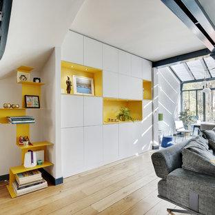 Cette image montre une petite salle de séjour design avec aucun téléviseur, un mur blanc, un sol en bois clair, aucune cheminée et un sol marron.