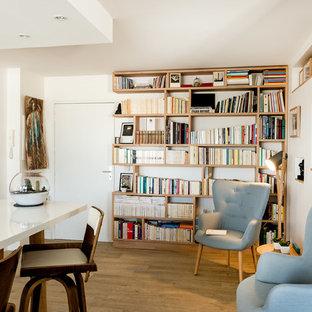 Cette image montre une salle de séjour avec une bibliothèque ou un coin lecture design ouverte avec un mur blanc, un sol en bois clair et un sol marron.