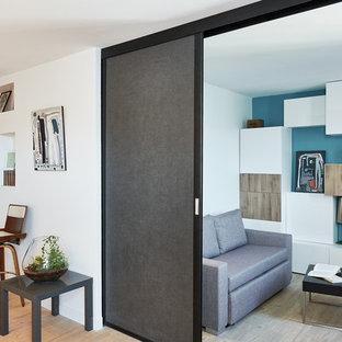 Cette photo montre une salle de séjour tendance avec un mur bleu, un sol en bois clair et un sol beige.