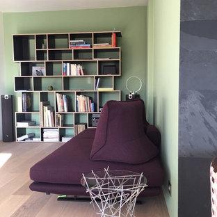 Cette image montre une salle de séjour avec une bibliothèque ou un coin lecture de taille moyenne et ouverte avec un mur vert, un sol en bois clair, aucune cheminée, un téléviseur fixé au mur et un sol beige.