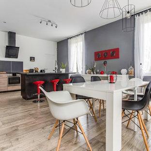 Idée de décoration pour une grande salle de séjour design ouverte avec un mur gris, sol en stratifié, un sol marron, aucune cheminée et aucun téléviseur.
