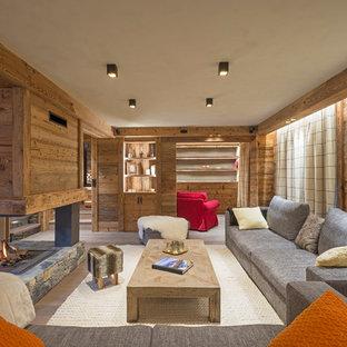 Inspiration pour une grande salle de séjour chalet ouverte avec un mur marron, un sol en bois brun, une cheminée double-face, un manteau de cheminée en bois et aucun téléviseur.