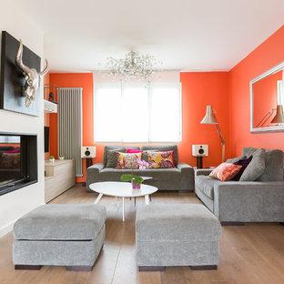 Idée de décoration pour une grand salle de séjour design ouverte avec un mur orange, un sol en bois brun, une cheminée standard et un téléviseur fixé au mur.