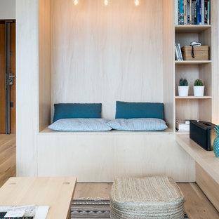 Cette photo montre une salle de séjour avec une bibliothèque ou un coin lecture scandinave avec un sol en bois clair.