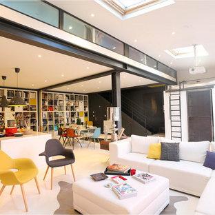 Idée de décoration pour une grande salle de séjour avec une bibliothèque ou un coin lecture design ouverte avec un mur blanc.