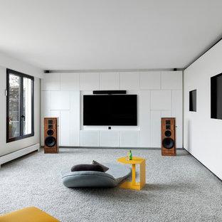 Idée de décoration pour une salle de séjour design de taille moyenne et fermée avec un mur blanc, moquette, un téléviseur fixé au mur, aucune cheminée et un sol gris.