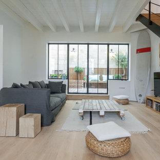 Modelo de sala de estar abierta, contemporánea, grande, sin chimenea, con paredes blancas, suelo de madera clara y televisor independiente