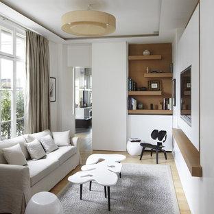 パリの中くらいの北欧スタイルのおしゃれなオープンリビング (白い壁、淡色無垢フローリング、暖炉なし、壁掛け型テレビ) の写真