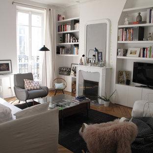 Idées déco pour une salle de séjour contemporaine de taille moyenne avec un mur blanc, un sol en bois brun, une cheminée standard, un manteau de cheminée en pierre et un téléviseur indépendant.