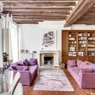 Cette photo montre une salle de séjour avec une bibliothèque ou un coin lecture méditerranéenne avec un mur blanc, un sol en carreau de terre cuite et une cheminée standard.