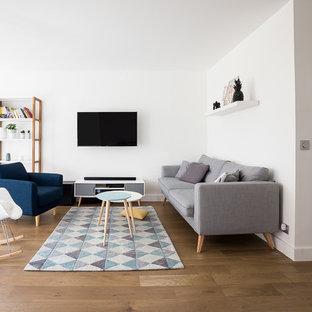パリの中くらいの北欧スタイルのおしゃれなオープンリビング (ライブラリー、白い壁、無垢フローリング、暖炉なし、壁掛け型テレビ) の写真