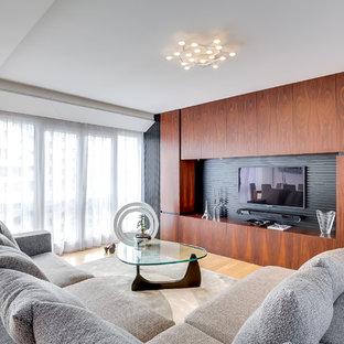 Cette image montre une salle de séjour design de taille moyenne et fermée avec un mur marron, un sol en bois brun et un téléviseur fixé au mur.