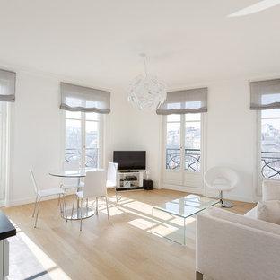 Idée de décoration pour une salle de séjour design de taille moyenne et ouverte avec un mur blanc, un sol en bois clair, aucune cheminée et un téléviseur indépendant.