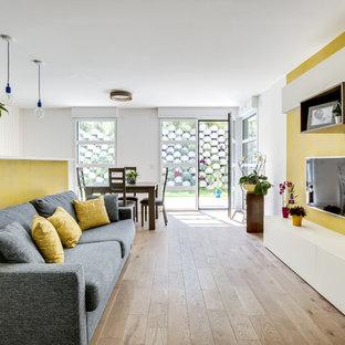 Immagine di un soggiorno contemporaneo aperto e di medie dimensioni con pareti gialle, parquet chiaro, TV a parete, nessun camino e pavimento marrone