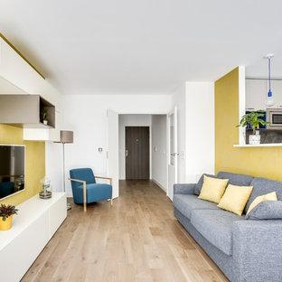 Diseño de sala de estar abierta, actual, pequeña, sin chimenea, con suelo de madera clara, televisor colgado en la pared, suelo marrón y paredes amarillas