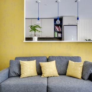 Immagine di un piccolo soggiorno minimal aperto con pareti gialle, parquet chiaro, TV a parete, pavimento marrone e nessun camino