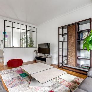 Cette image montre une grande salle de séjour design ouverte avec un mur blanc, un téléviseur indépendant, un sol en bois brun et aucune cheminée.