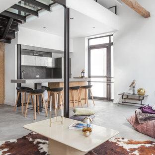 Cette image montre une grande salle de séjour design ouverte avec un mur blanc, béton au sol et aucune cheminée.