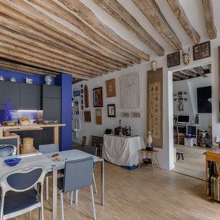 Réalisation d'une grande salle de séjour ethnique ouverte avec un mur blanc, un sol en bois clair, un sol beige, aucune cheminée et aucun téléviseur.