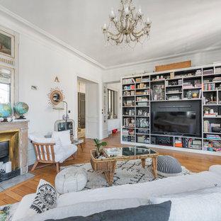 Idée de décoration pour une salle de séjour avec une bibliothèque ou un coin lecture bohème fermée avec un mur blanc, un sol en bois brun, une cheminée standard et un téléviseur encastré.