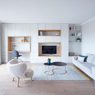 Cette photo montre une salle de séjour avec une bibliothèque ou un coin lecture scandinave ouverte avec un mur gris, un sol en bois clair, aucune cheminée, un téléviseur encastré et un sol beige.
