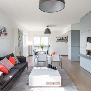 Idées déco pour une grande salle de séjour contemporaine ouverte avec un mur gris, un sol en bois clair, un téléviseur dissimulé et aucune cheminée.