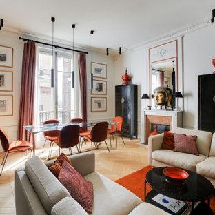 パリの大きいコンテンポラリースタイルのおしゃれなオープンリビング (白い壁、淡色無垢フローリング、標準型暖炉、レンガの暖炉まわり、ベージュの床) の写真