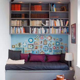 Cette image montre une petite salle de séjour avec une bibliothèque ou un coin lecture bohème fermée avec un sol en bois brun, aucune cheminée, aucun téléviseur et un mur multicolore.